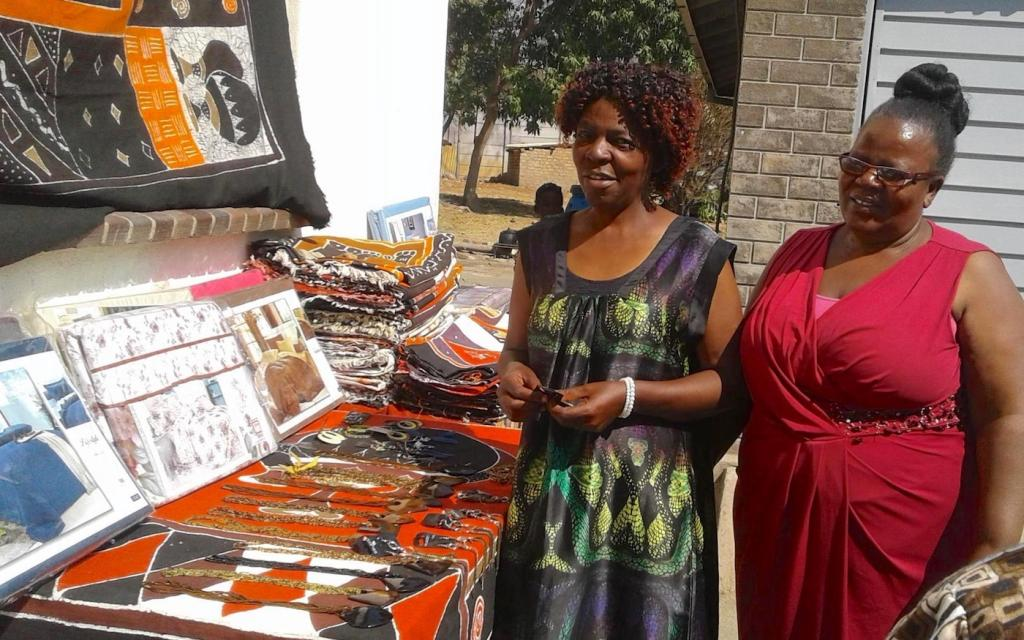 Judy (left) with a customer and a table of her products