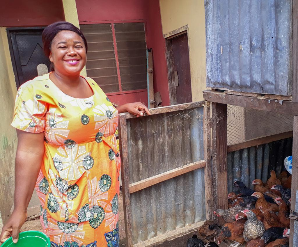 Sewuse standing by her birds